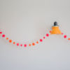 pom pom festival garland with orange and pink pom poms