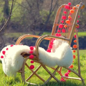 PomPom Galore Festival Orange & Pink combo neon pompoms on chair with sheepskin