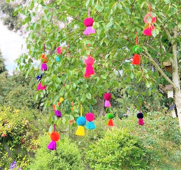 Jumbo pom pom tassel swags hanging in a tree