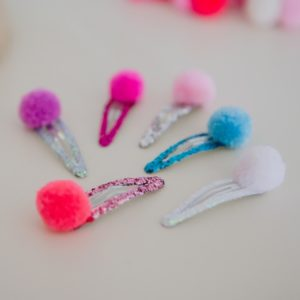 pom pom glitter hair slides in colour pairs on very shiny glitter hair sldies